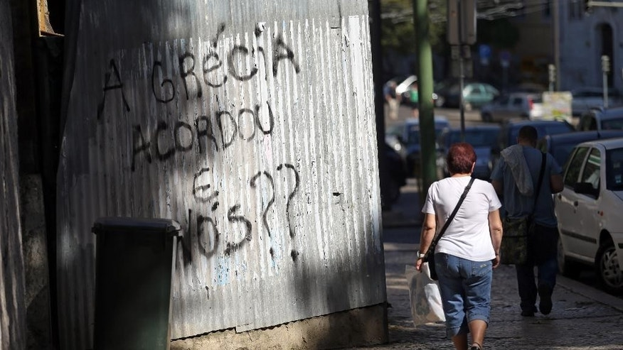 "People walk past a graffiti that reads in Portuguese: ""Greece woke up, what about us?"" in Lisbon, Thursday, May 21, 2015. European Central Bank head Mario Draghi said that ""growth is too low everywhere"" in Europe despite a modest recovery, during an ECB's conference on inflation and unemployment in Sintra, Portugal. (AP Photo/Francisco Seco)"