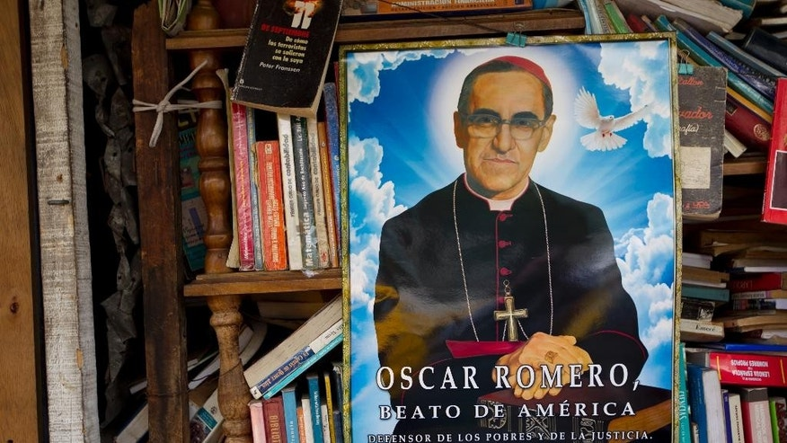 A portrait of Roman Catholic Archbishop Oscar Romero decorates a used book stand near the Metropolitan Cathedral in San Salvador, El Salvador, Thursday, May 21, 2015. A Mass will be held in Plaza El Salvador del Mundo on Saturday for Romero's beatification ceremony, a first step toward canonization and sainthood. (AP Photo/Moises Castillo)