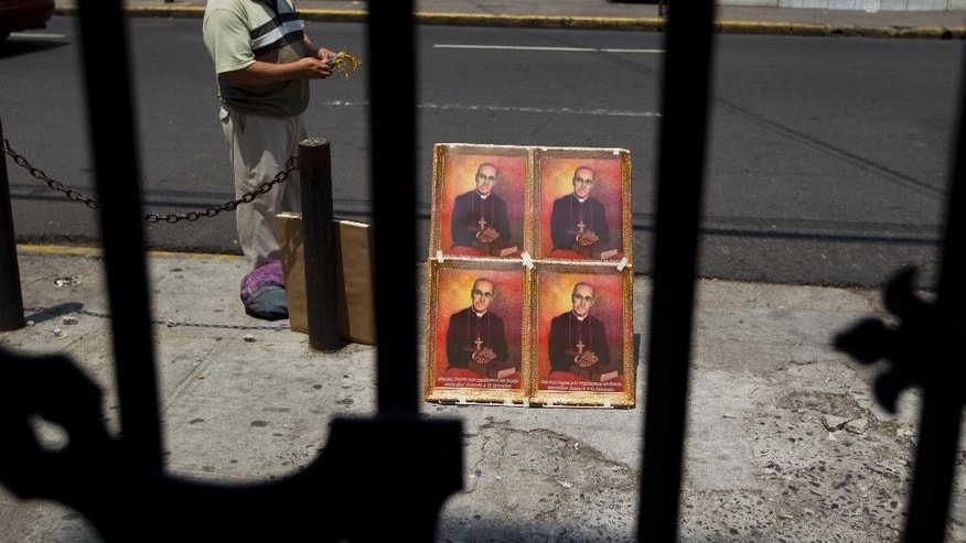 A street vendor stands next to portraits for sale of Roman Catholic Archbishop Oscar Romero outside the Cathedral in San Salvador, El Salvador, Thursday, May 21, 2015. A Mass will be held in Plaza El Salvador del Mundo on Saturday for Romero's beatification ceremony, a first step toward canonization and sainthood. (AP Photo/Moises Castillo)