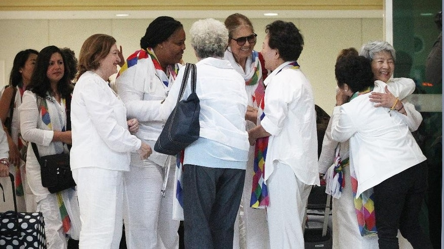 From third left, Nobel Peace Prize laureates, Mairead Maguire, Leymah Gbowee and U.S. activist Gloria Steinem, fourth right, are greeted by South Korean activists upon their arrival from North Korea at the office of the customs, immigration and quarantine in Paju, South Korea, near the border village of Panmunjom,  Sunday, May 24, 2015. International women activists including Steinem and two Nobel Peace laureates on Sunday were denied an attempt to walk across the Demilitarized Zone dividing North and South Korea, but were allowed to cross by bus and complete what one of them called a landmark peace event.(AP Photo/Ahn Young-joon)
