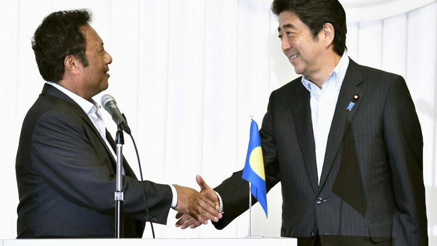 Japanese Prime Minister Shinzo Abe, right, shakes hands with Palau's President Tommy Remengesau, co-chairman of the 7th Pacific Islands Leaders Meeting, at the closing of a two-day meeting in Iwaki, Fukushima Prefecture, northeastern Japan Saturday, May 23, 2015. Japan pledged Saturday 55 billion yen ($450 million) in aid to Pacific island nations that are battling rising sea levels and natural calamities as a result of global warming. (Shigeyuki Inakuma/Kyodo News via AP) JAPAN OUT, CREDIT MANDATORY