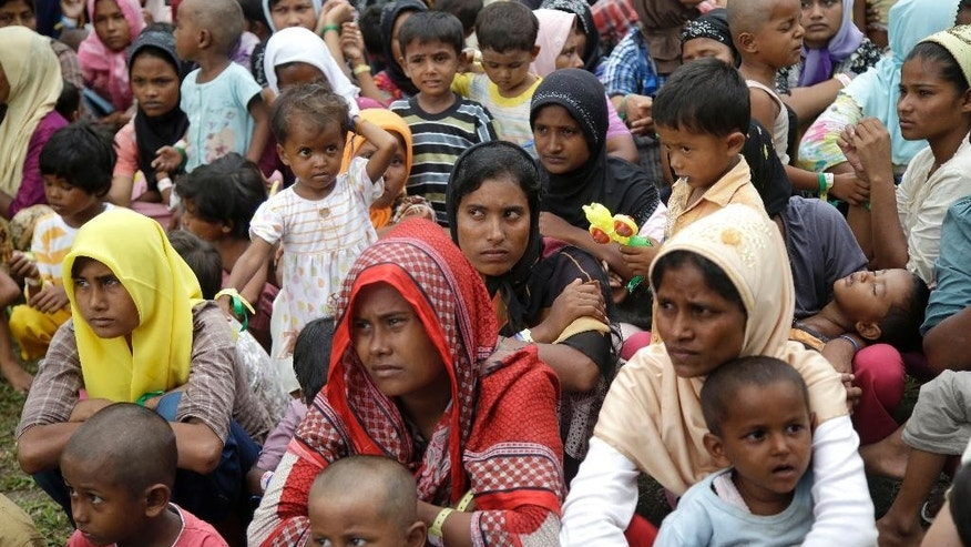 Ethnic Rohingya women and children gather to receive meal at a temporary shelter in Bayeun, Aceh province, Indonesia, Saturday, May 23, 2015. Myanmar's president has signed off on a law requiring some mothers to space their children three years apart despite objections by a visiting senior U.S. diplomat and rights activists, who worry it could be used not only to repress women, but also religious and ethnic minorities. As predominantly Buddhist Myanmar started moving from dictatorship to democracy four years ago, newfound freedoms of expression lifted the lid on deep-seeded hatred for minority Muslims - including Rohingya Muslims now arriving on Southeast Asian shores in crowded, rickety boats. (AP Photo/Tatan Syuflana)