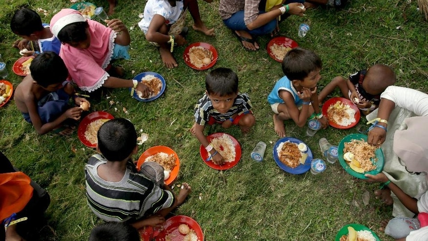 Ethnic Rohingya children eat food at a temporary shelter in Bayeun, Aceh province, Indonesia Saturday, May 23, 2015. Myanmar's president has signed off on a law requiring some mothers to space their children three years apart despite objections by a visiting senior U.S. diplomat and rights activists, who worry it could be used not only to repress women, but also religious and ethnic minorities. As predominantly Buddhist Myanmar started moving from dictatorship to democracy four years ago, newfound freedoms of expression lifted the lid on deep-seeded hatred for minority Muslims - including Rohingya Muslims now arriving on Southeast Asian shores in crowded, rickety boats. (AP Photo/Tatan Syuflana)