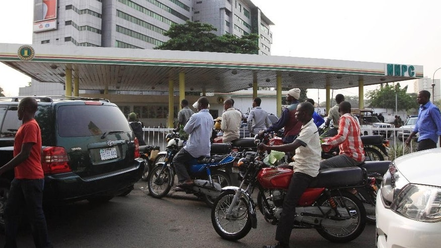 FILE -  In this Wednesday Jan. 11, 2012, file photo, people line up to buy fuel at a government petrol station on the third day of nation wide strike following the removal of a fuel subsidy in Lagos, Nigeria. Nigerian airlines grounded flights Saturday, May 23, 2015, as a months-long fuel shortage worsened, aggravated by a strike disrupting fuel deliveries in Africa's biggest oil producer. Vehicles also were grounded. Normally bustling roads in Lagos, a metropolis of 20 million, were half-empty and gas stations closed Saturday. (AP Photo/Sunday Alamba, file)