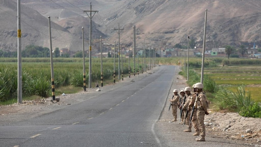 FILE - This May 15, 2015 file photo shows soldiers standing guard on a highway that was the site of protests against the Tia Maria project near Cocachacra, Peru. Late Friday, May 22, the government announced a 60-day state of emergency, suspending the rights of assembly, the freedom of movement and protection against searches without a warrant. Farmers are opposed to the Mexican-owned Southern Peru Copper mining project because they fear it would contaminate their crops. (AP Photo/Martin Mejia, File)