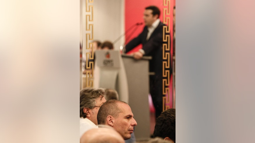 "Greece's Finance Minister Yanis Varoufakis, center, listens to a speech by Prime Minister Alexis Tsipras during a Syriza party central committee meeting in Athens, Greece, on Saturday, May 23, 2015. Tsipras has told leaders of the governing Radical Left Coalition that Greece is ready to accept a ""viable and long lasting"" deal with its lenders, but not on ""humiliating terms."" (AP Photo/Yorgos Karahalis)"