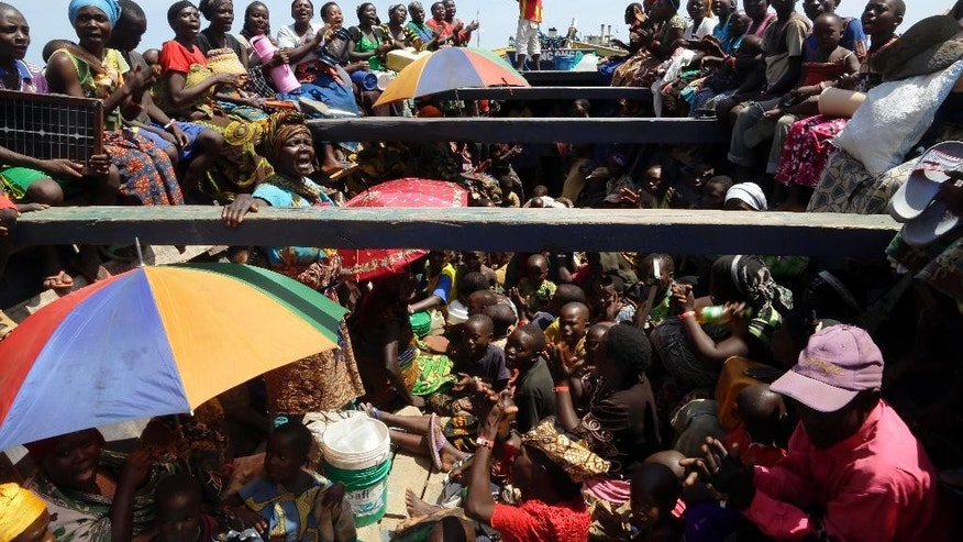 Refugees who fled Burundi's violence and political tension sing in a  speedboat taking  them to a ship freighted by the UN, at Kagunga on Lake Tanganyika, Tanzania, Saturday, May 23, 2015 to be taken to the port city of Kigoma. An outbreak of cholera has infected 3,000 people in a Tanzanian border region where refugees fleeing political unrest in Burundi have massed, the U.N. Refugee Agency said Friday, May 22, 2015. Some 300 to 400 new cases of cholera are being reported daily. At least 31 people — 29 refugees and two Tanzanians — already have died of the disease, according to UNHCR. More than 64,000 Burundians have fled to Tanzania in recent weeks, UNHCR said, escaping the unrest sparked by their president's bid for a third term that many say is unconstitutional. (AP Photo/Jerome Delay)