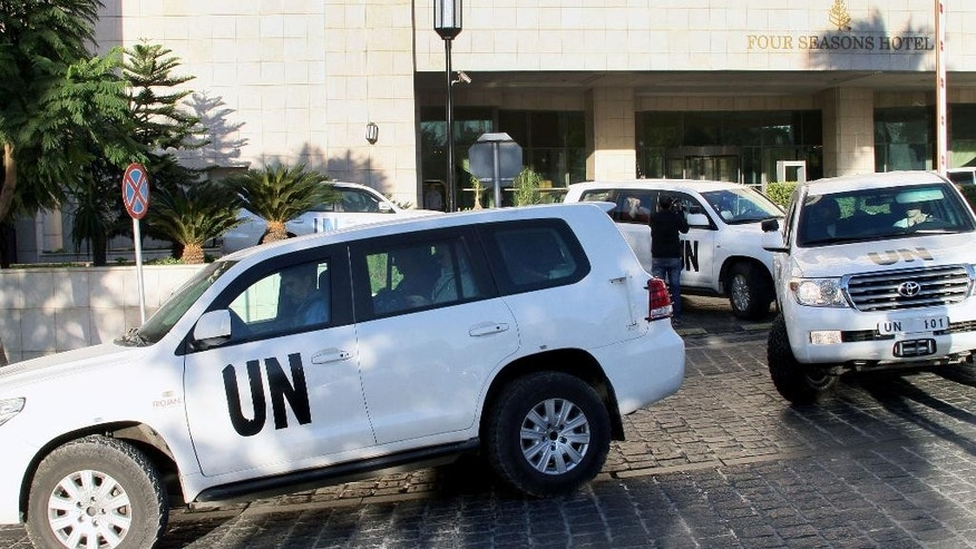 FILE - In this Oct. 8, 2013 file photo, a convoy of chemical weapons disarmament experts depart the Four Seasons Hotel in Damascus, Syria. Two years after President Bashar Assad agreed to destroy his chemical arsenal and joined the Chemical Weapons Convention, activists said they have documented 18 cases of chlorine gas used in the country's rebel-held north since March 6, 2015, when the U.N. issued a resolution determining that chlorine was used in Syria and warning of repercussions. (AP Photo, File)