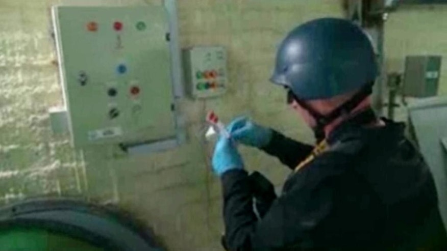 FILE - This file image made from video broadcast on Syrian State Television on Tuesday, Oct. 8, 2013, purports to show a chemical weapons expert taking samples at a chemical weapons plant at an unknown location in Syria. Two years after President Bashar Assad agreed to destroy his chemical arsenal and joined the Chemical Weapons Convention, activists said they have documented 18 cases of chlorine gas used in the country's rebel-held north since March 6, 2015, when the U.N. issued a resolution determining that chlorine was used in Syria and warning of repercussions. (AP Photo/Syrian State Television via AP video, File)