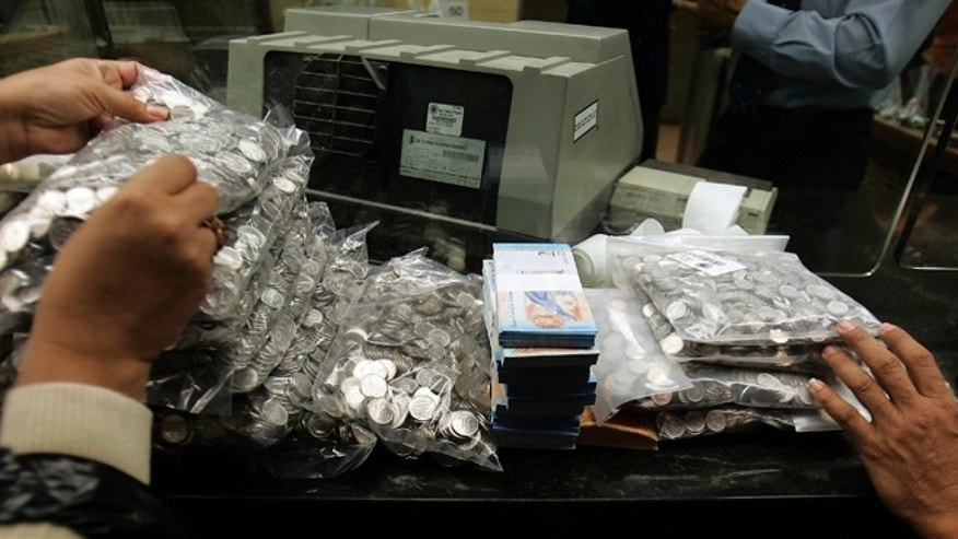 "FILE - This Jan. 4, 2008 file photo shows bank workers handling Venezuela's currency, the ""Bolivar Fuerte,"" or Strong Bolivar, at the Central Bank in Caracas, Venezuela. Venezuelans are expressing disbelief as the countrys currency has lost a quarter of its value on the black market in the space of a week in 2015, between May 14 and 22. (AP Photo/Fernando Llano, File)"