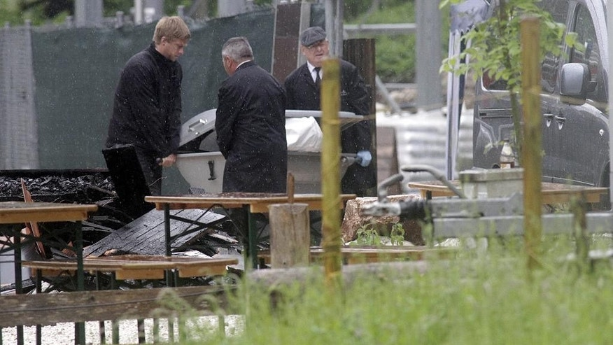 In this Saturday May 23, 2015 picture  undertakers carry a coffin out of a house  in the Bavarian town of Schneizlreuth , Germany. Police in Germany say they have recovered the bodies of six people killed in the fire at the  guesthouse in the Alps. The men were among a group of 47 employees of the Bavarian construction company Lindner who had been staying at the converted farmhouse in Schneizlreuth, southeast of Munich. Forty-one people managed to flee the fire, which broke out in the early hours of Saturday. Seven people were hospitalized with serious injuries.  ( Ferdinand Farthofer/aktivnews/dpa  via AP)