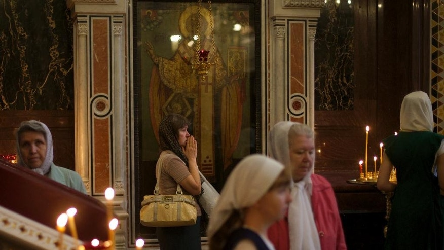 A Russian Orthodox believer prays during the religious service to mark the Day of St. Cyril and Methodius, founders of the Cyrillic alphabet, in the Christ The Saviour Cathedral in Moscow, Russia, on Sunday, May 24, 2015. (AP Photo/Ivan Sekretarev)