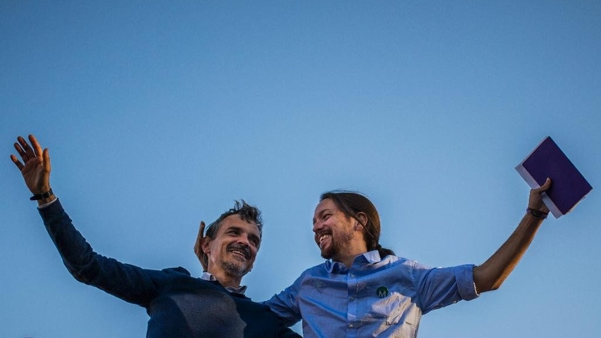 Pablo Iglesias, right, the leader of Spain's new and growing left wing 'Podemos' (We Can) party, stands with Podemos candidate for President of the Community of Madrid Jose Manuel Lopez, as they salute the crowd during a meeting with supporters for the upcoming local elections in Madrid, Spain, Friday, May 22, 2015. Spain could be set for a political upheaval in key local elections this weekend, with strong signs that voters fed up with economic crisis and corruption scandals may punish both the ruling conservative Popular Party and the leading opposition Socialists. (AP Photo/Andres Kudacki)
