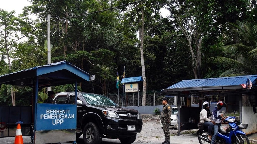 May 24, 2015: Malaysian Anti-Smuggling Unit officers check on vehicles at the entry point of Malaysia - Thailand border in Wang Kelian, Malaysia.