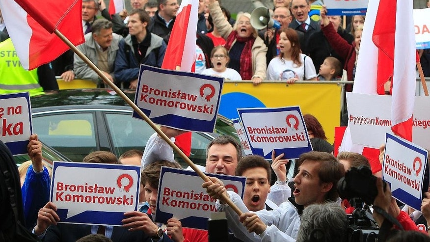 Supporters of Bronislaw Komorowski and Andrzej Duda react in front of a tv studio during the second debate between opposition candidate Andrzej Duda,  and incumbent Bronislaw Komorowski ahead of the May 24 presidential runoff  in Warsaw, Poland, Thursday, May 21, 2015.(AP Photo/Czarek Sokolowski)