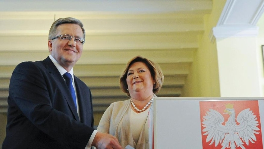 Polish President Bronislaw Komorowski casts his ballot as wife Anna looks on, during the presidential runoff election  at a polling station in Warsaw, Poland, Sunday, May 24, 2015. Poles were voting Sunday in the final round of a cliffhanger presidential election race between the conservative incumbent Bronislaw Komorowski and an even more conservative challenger Andrzej Duda from the Law and Justice party .  (AP Photo/Alik Keplicz)