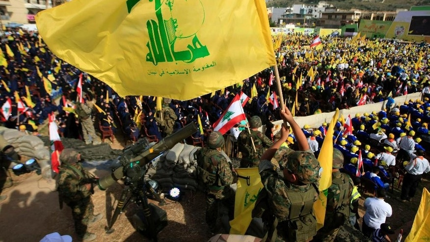 "A Hezbollah fighter waves its flag as other fighters stand guard during a rally commemorating ""Liberation Day,"" which marks the withdrawal of the Israeli army from southern Lebanon in 2000, in the southern town of Nabatiyeh, Lebanon, Sunday, May 24, 2015. Nasrallah said Sunday that the region is facing ""unprecedented danger"" from extremist groups and vowed his militants will expand their involvement in Syria's civil war in support of government forces.  (AP Photo/Mohammed Zaatari)"