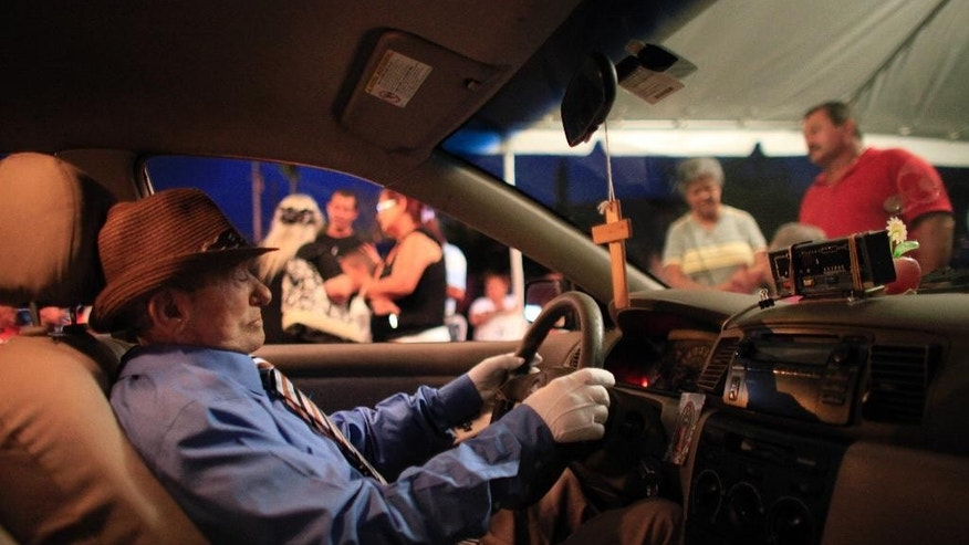 The body of Victor Perez Cardona is propped up inside his taxi during his wake in Aguas Buenas, Puerto Rico, Sunday, May 24, 2015. Perez Cardona, 73, a cancer patient and a veteran taxi driver known in the town of Aguas Buenas as 'Vitín the driver', joined the unusual tradition of wakes to honor his profession being veiled as if he were driving his taxi. (AP Photo/Ricardo Arduengo)