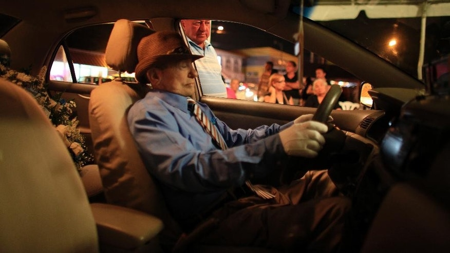Rafael Perez Cardona, looks his brother Victor Perez Cardona,  whose body was propped up inside his taxi in Aguas Buenas, Puerto Rico, Sunday, May 24, 2015. Perez Cardona, 73, a cancer patient and a veteran taxi driver known in the town of Aguas Buenas as 'Vitín the driver', joined the unusual tradition of wakes to honor his profession being veiled as if he were driving his taxi. (AP Photo/Ricardo Arduengo)