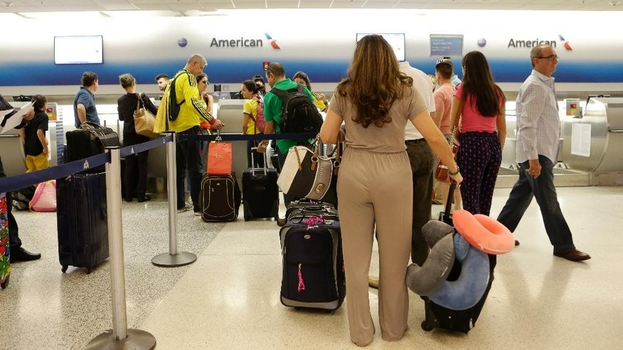 FILE - In this June 25, 2014, file photo, passengers wait in line at the American Airlines International counter at Miami International Airport in Miami. American Airlines announced that it had stopped accepting Venezuelan bolivars for any of its 19 weekly flights out of Venezuela. Customers must now use a foreign credit card to buy the tickets online. Virtually all other foreign carriers have made the same switch with the government's consent, according to the Venezuela Airlines Association. (AP Photo/Alan Diaz, File)