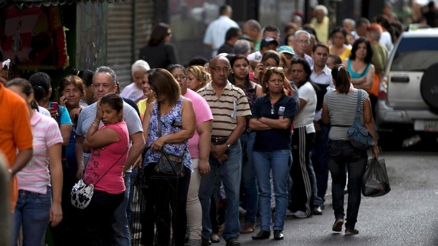 FILE - In this Jan. 8, 2015, file photo, shoppers queue outside of a supermarket in downtown Caracas, Venezuela. Venezuelans continue to struggle to find basic goods including detergent and sugar. Most of the shortages in Venezuela are driven in part by the country's tight currency controls, which make it hard to get dollars at a subsidized rate for imports while creating a thriving black market for currency. (AP Photo/Fernando Llano, File)