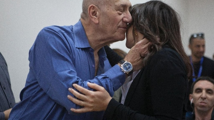 Former Israeli Prime Minister Ehud Olmert embraces a woman at the Jerusalem District Court, Monday, May 25, 2015. Olmert was sentenced Monday to eight months in prison for unlawfully accepting money from a U.S. supporter, capping the dramatic downfall of a man who only years earlier led the country and hoped to bring about a historic peace agreement with the Palestinians. (Heidi Levine/Pool Photo via AP)