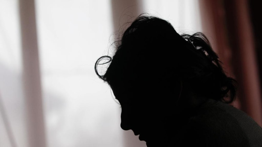 In this March 2, 2015 photo, Klara Balogova is silhouetted against a window at a Roma settlement near Kralovsky Chlmec, Slovakia. Balogova was 18, penniless and pregnant when she rode thousands of miles from Slovakia to England to marry a man she had never met. Each year, dozens of women from the poorer corners of eastern Europe are lured to travel to western Europe for sham marriages with men who pay large sums because they want to live, work or claim benefits more easily in their chosen country and move freely within Europe. (AP Photo/Petr David Josek)