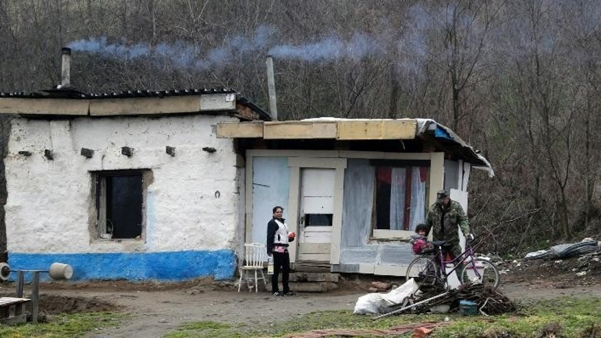 In this March 2, 2015 photo, a Roma family stands outside their hut in a settlement near Kralovsky Chlmec, Slovakia. Each year, dozens of women from the poorer corners of eastern Europe are lured to travel to western Europe for sham marriages with men who pay large sums because they want to live, work or claim benefits more easily in their chosen country and move freely within Europe. (AP Photo/Petr David Josek)