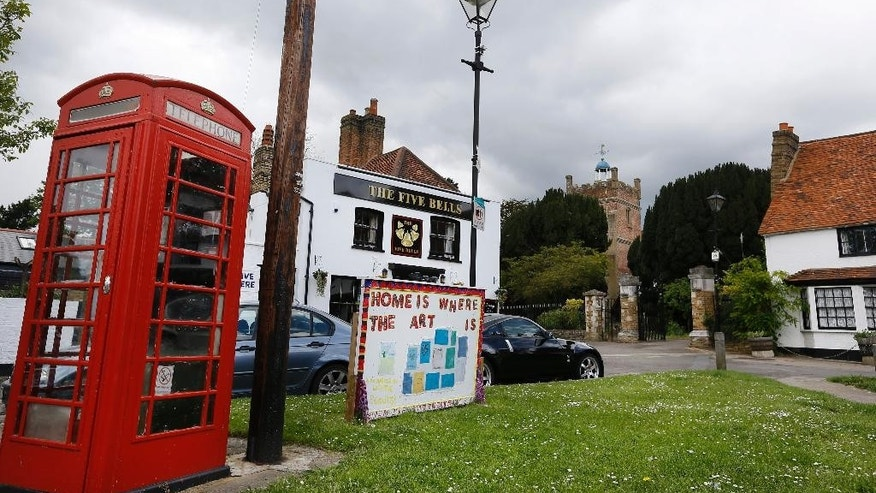 In this photo taken on Tuesday, May 19, 2015, cars are parked in the center of the village in Harmondsworth in London. Residents of the village close to Heathrow Airport are campaigning against the expansion of the airport which they claim will decimate their community.  (AP Photo/Kirsty Wigglesworth)