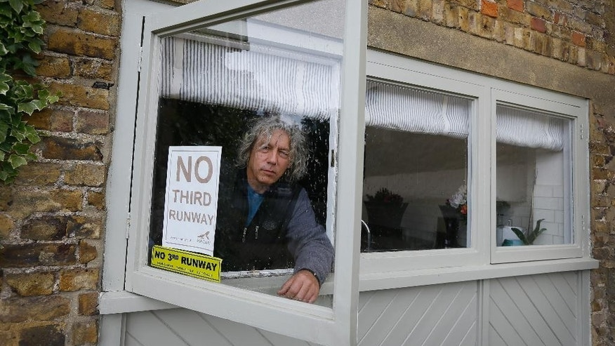 In this photo taken on Tuesday, May 19, 2015, Neil Keveren looks out of the window of his home in Harmondsworth in London. Residents of the village close to Heathrow Airport are campaigning against the expansion of the airport which they claim will decimate their community. (AP Photo/Kirsty Wigglesworth)