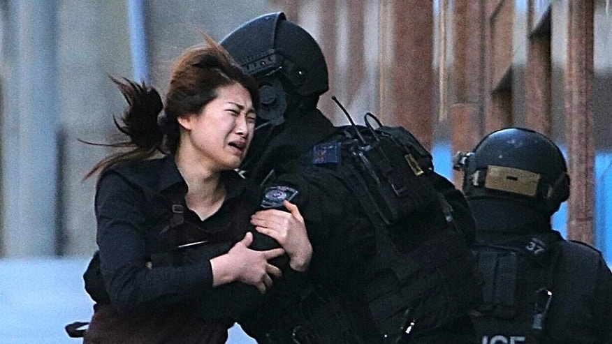FILE - In this Dec. 15, 2014 file photo, a hostage runs to an armed tactical response police officers for safety after she escaped from a cafe under siege at Martin Place in the central business district of Sydney, Australia.  The man who took 18 people hostage at a Sydney cafe last year was educated and erratic, secretive about his own life and public about his many grievances, and a self-obsessed fabulist who grew increasingly defiant as he edged closer to launching his deadly attack, lawyers told an inquest Monday, May 25, 2015. (AP Photo/Rob Griffith, File)