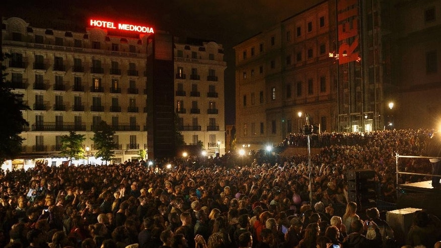 People attend a speech by Pablo Iglesias, leader of the Podemos (We Can) party celebrating the party results after the elections and in support of local candidate for Ahora Madrid (Madrid Now) party in Madrid, Spain, Sunday, May 24, 2015. Ahora Madrid stood for the Madrid municipal elections to seek an end nearly four decades of dominance by the conservative Popular Party and the center-left Socialists.(AP Photo/Daniel Ochoa de Olza)