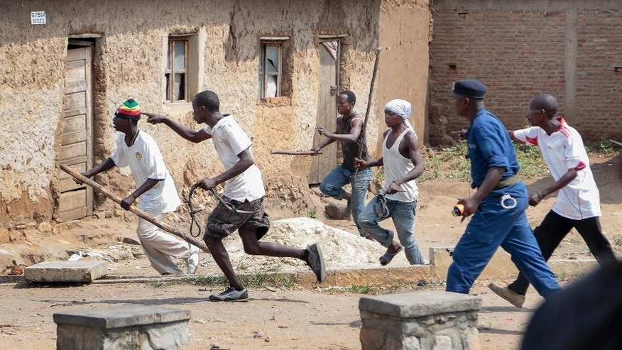 Members of the Imbonerakure pro-government youth militia chase after opposition protesters, unhindered by police, in the Kinama district of the capital Bujumbura, in Burundi Monday, May 25, 2015. Protests continued in the capital Monday, with demonstrators saying they will continue until President Pierre Nkurunziza steps down at the end of his second term. (AP Photo/Berthier Mugiraneza)