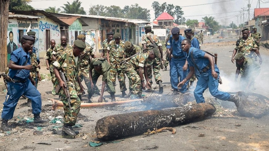 Police and army clear barricades set by opposition demonstrators in the Cibitoke district of the capital Bujumbura, in Burundi Monday, May 25, 2015. Protests continued in the capital Monday, with demonstrators saying they will continue until President Pierre Nkurunziza steps down at the end of his second term. (AP Photo/Berthier Mugiraneza)
