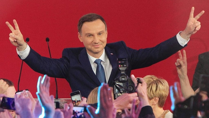 Opposition candidate Andrzej Duda celebrates with supporters his victory, as first exit polls in the presidential runoff voting are announced in Warsaw, Poland, Sunday, May 24, 2015. Polish President Bronislaw Komorowski conceded defeat in the presidential election Sunday after an exit poll showed him trailing Duda, a previously little-known right-wing politician. (AP Photo/Czarek Sokolowski)