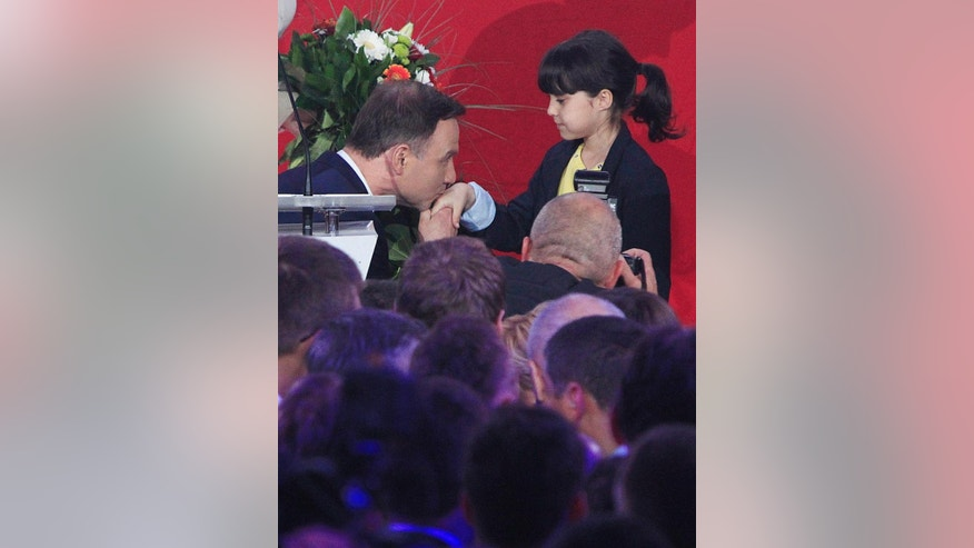 Opposition candidate Andrzej Duda kisses hand of the girl who gave him flowers during celebrates with supporters his victory, as first exit polls in the presidential runoff voting are announced in Warsaw, Poland, Sunday, May 24, 2015. Polish President Bronislaw Komorowski conceded defeat in the presidential election Sunday after an exit poll showed him trailing Duda, a previously little-known right-wing politician. (AP Photo/Czarek Sokolowski)