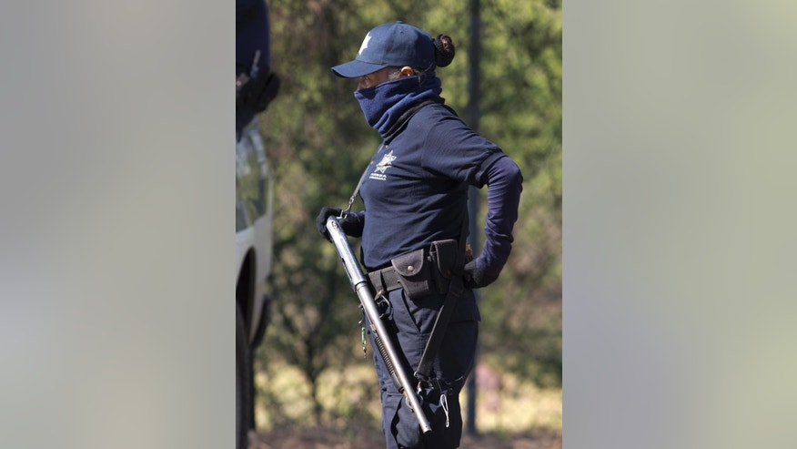 A masked police officer stands guard just inside the entrance of Rancho del Sol, a ranch that was the site of clashes between Mexican authorities and a drug cartel, in the municipality of Ecuandureo, Mexico, Saturday, May 23, 2015. The clash was the deadliest confrontation in recent memory, with 42 suspected gang gunmen and one Federal Police officer killed during a three-hour firefight on Friday at this remote western ranch. (AP Photo/Eduardo Verdugo)