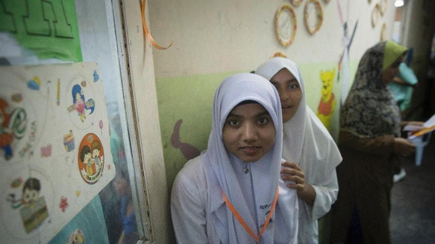 In this May 21, 2015 photo, Azimah Mohd Jalil, 15, a Rohingya girl, poses for a photo outside her classroom at a Rohingya Education Center in Klang, Malaysia. With more work opportunities than Indonesia and a more Muslim-friendly environment than Thailand, Malaysia has long been the destination of choice for Rohingya Muslims fleeing persecution in Myanmar.  (AP Photo/Vincent Thian)