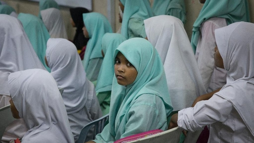 In this May 21, 2015 photo, Rohingya school girls watch teacher day celebrations outside their classroom at a Rohingya Education Center in Klang, Malaysia. With more work opportunities than Indonesia and a more Muslim-friendly environment than Thailand, Malaysia has long been the destination of choice for Rohingya Muslims fleeing persecution in Myanmar.  (AP Photo/Vincent Thian)
