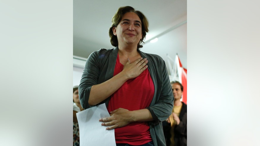 The leader of leftist coalition Barcelona Together, Ada Colau, gestures after her party's success in the elections in Barcelona, Spain, Sunday, May 24, 2015. New parties won strong support in Spain's local elections Sunday as voters turned their back on the country's traditional political heavyweights, an exit poll indicated. There was also an upset in Barcelona, where a popular anti-eviction campaigner backed by We Can was poised to unseat the region's long dominant and conservative Convergence and Union party. (AP Photo/Manu Fernandez)