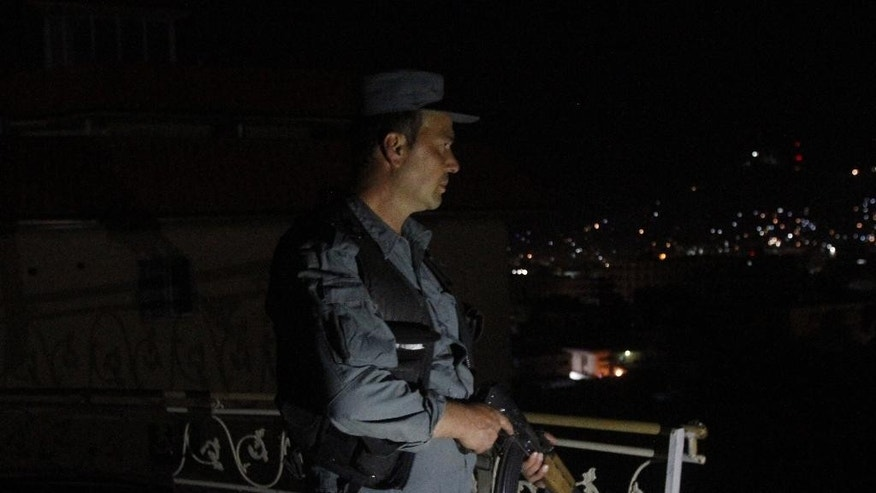 An Afghan security officer takes a position at a house near an ongoing attack on a guesthouse in Kabul Afghanistan, Wednesday, May 27, 2015. Heavy gunfire and explosions echoed through an upscale neighborhood in Afghanistan's capital late Tuesday night, as police surrounded a guesthouse popular with foreigners thought to be under attack by insurgents. (AP Photo/Allauddin Khan)
