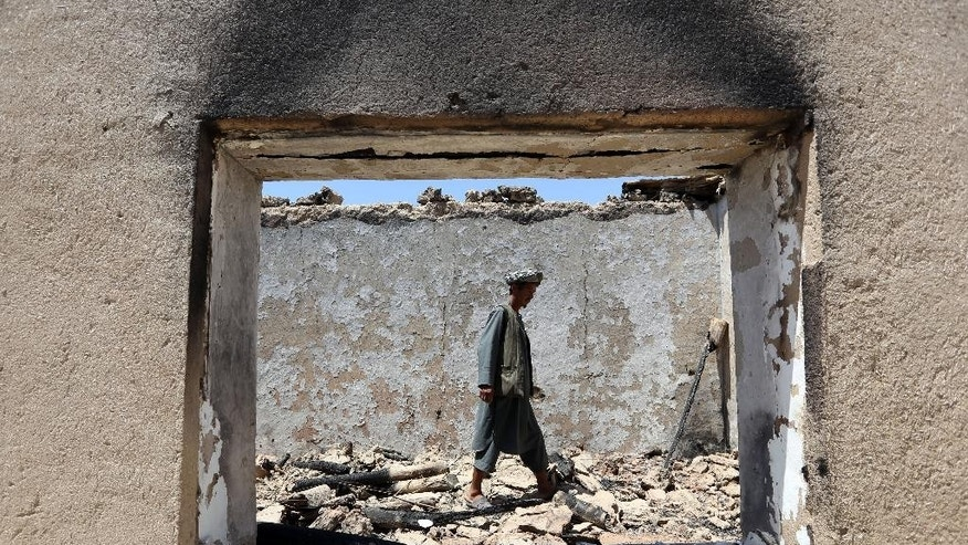 In this Thursday, May 21, 2015 photo, an Afghan villager checks a building torched by Taliban fighters at Talawka village in Kunduz province, north of Kabul, Afghanistan. Fighting has been raging in Kunduz for more than a month. Pushed back by army reinforcements that arrived days after the assault began, insurgents now occupy villages in Gor Tepa, 15 kilometers (12 miles) from the provincial capital, also called Kunduz. (AP Photo/Rahmat Gul)
