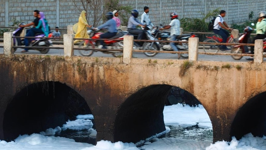 In this Monday, May 25, 2015, file photo, traffic moves on a bridge over Bellundur Lake which is filled with froth from industrial pollution in Bangalore, India, Monday, May 25, 2015. Indian prime minister Narendra Modi's first year in office was punctuated with promises of clear rivers, clean energy and toilets for all, but environmentalists worry his government is on an entirely different path: dismantling hard-won environmental laws in the name of boosting growth. (AP Photo/Aijaz Rahi)