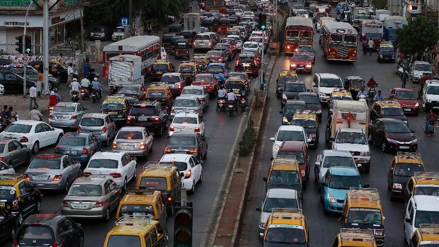 In this Monday, May 25, 2015, photo, traffic clogs a road in Mumbai, India. Indian prime minister Narendra Modi's first year in office was punctuated with promises of clear rivers, clean energy and toilets for all, but environmentalists worry his government is on an entirely different path: dismantling hard-won environmental laws in the name of boosting growth. (AP Photo/Rajanish Kakade)