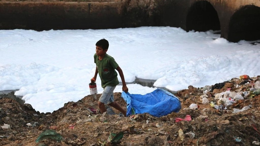 In this Monday, May 25, 2015, photo, a young garbage collector looks for valuables in the garbage dumped on the banks of Bellundur Lake, which is filled with froth from industrial pollution in Bangalore, India.  Indian prime minister Narendra Modi's first year in office was punctuated with promises of clear rivers, clean energy and toilets for all, but environmentalists worry his government is on an entirely different path: dismantling hard-won environmental laws in the name of boosting growth. (AP Photo/Aijaz Rahi)