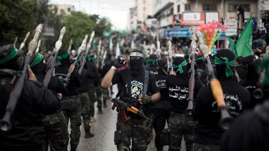 FILE - In this Dec. 14, 2014, file photo, masked Palestinian gunmen of the Hamas militant group stand during a rally to commemorate the 27th anniversary of the group in Gaza City. Amnesty International on Wednesday, May 27, 2015, accused the militant group of abducting, torturing and killing Palestinians during the war in the Gaza Strip summer 2014, saying some of the actions amount to war crimes. (AP Photo/Khalil Hamra, File)