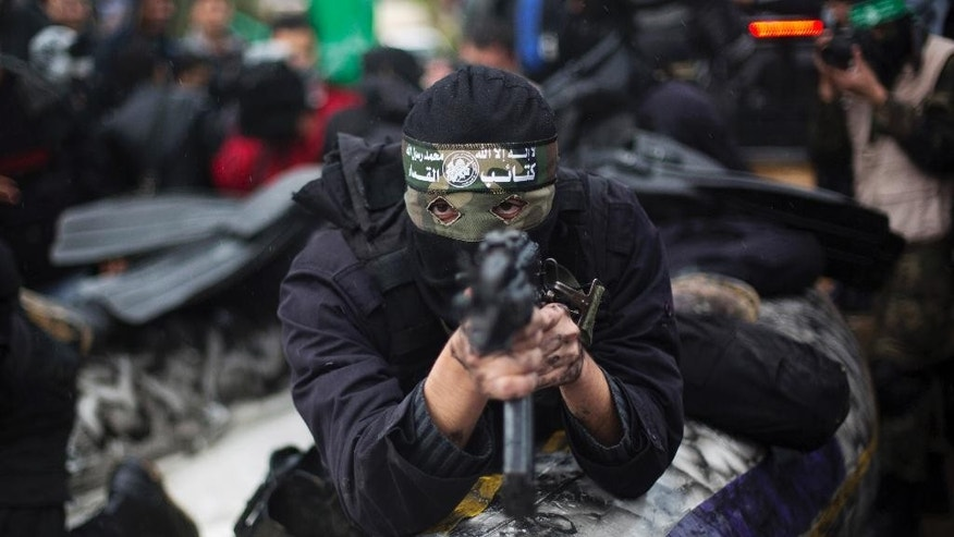 FILE - In this Dec. 14, 2014, file photo, a masked Palestinian gunman of the Hamas militant group holds a weapon during a rally to commemorate the 27th anniversary of the group in Gaza City. Amnesty International on Wednesday, May 27, 2015, accused the militant group of abducting, torturing and killing Palestinians during the war in the Gaza Strip summer 2014, saying some of the actions amount to war crimes. (AP Photo/Khalil Hamra, File)