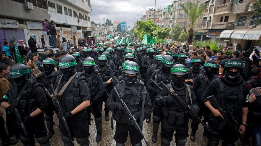 FILE - In this Dec. 14, 2014, file photo, masked Palestinian gunmen of the Hamas militant group hold weapons during a rally to commemorate the 27th anniversary of the group in Gaza City. Amnesty International on Wednesday, May 27, 2015, accused the militant group of abducting, torturing and killing Palestinians during the war in the Gaza Strip summer 2014, saying some of the actions amount to war crimes. (AP Photo/Khalil Hamra, File)
