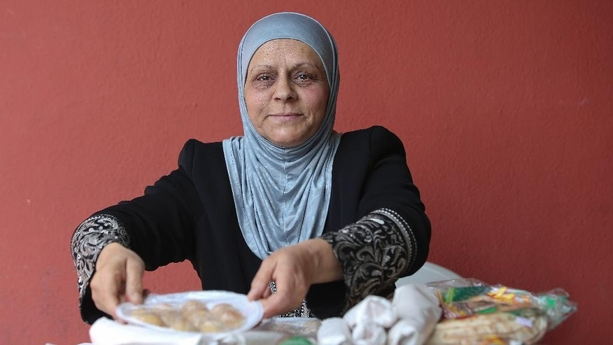 In this May 15, 2015 photo, Syrian refugee Dalaz Chora sells Arabic food outside a mosque in Sao Paulo, Brazil. Brazil's National Committee for Refugees said around 1,900 Syrian refugees have arrived in the county to take advantage of measures adopted about two years ago that eased their entry. (AP Photo/Andre Penner)