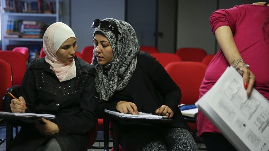 In this May 20, 2015 photo, Syrian refugees Shahrazad Dakkak, left, and Elham Abu Alainain, attend a Portuguese language class at Adus, a refugee reintegration institute in Sao Paulo, Brazil. Refugees from Syria and other countries receive help at the non-governmental Refugee Integration Institute in Sao Paulo. The institute's director, Marcelo Haydu, said the refugees are offered professional and Portuguese-language courses to help them enter the job market. (AP Photo/Andre Penner)
